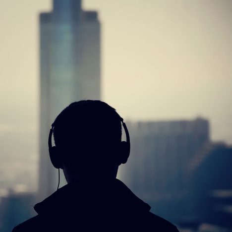 Silhouette of man wearing headphones overlooking office skyscrapers